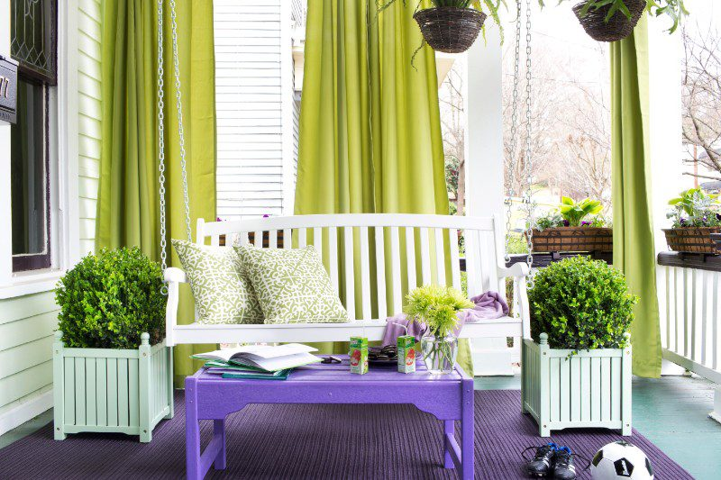 green outdoor curtains on front porch with porch swing