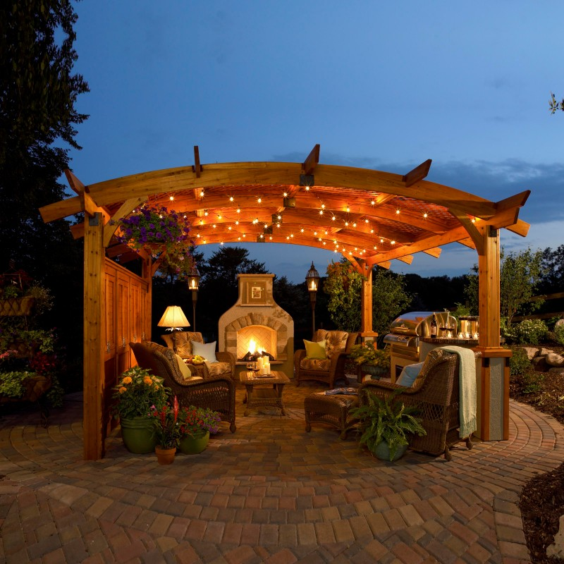 wood pergola with outdoor fireplace and string lights