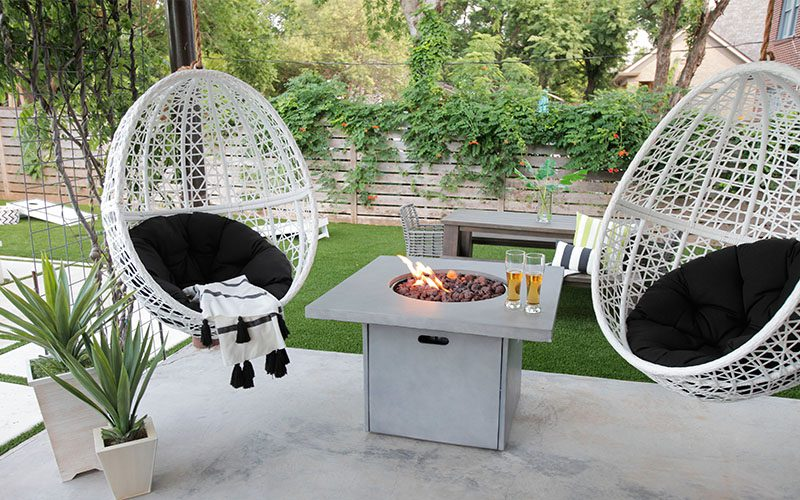 white hanging egg chairs with black cushions