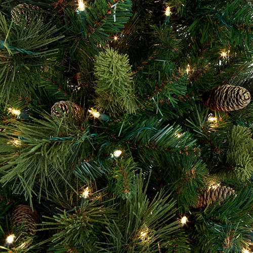 close up of artificial christmas tree with pine cones