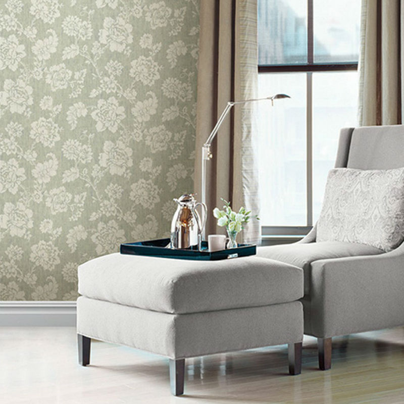White chair and ottoman set against light green floral wallpaper