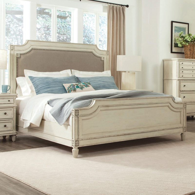 cottage style white wood bed with upholstered headboard
